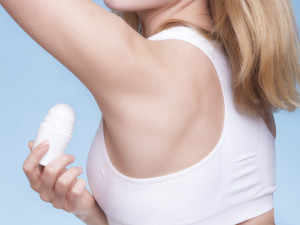 Part of female body. Girl applying stick deodorant in armpit. Young woman putting antiperspirant in underarms on blue. Daily skin care and hygiene. Studio shot.